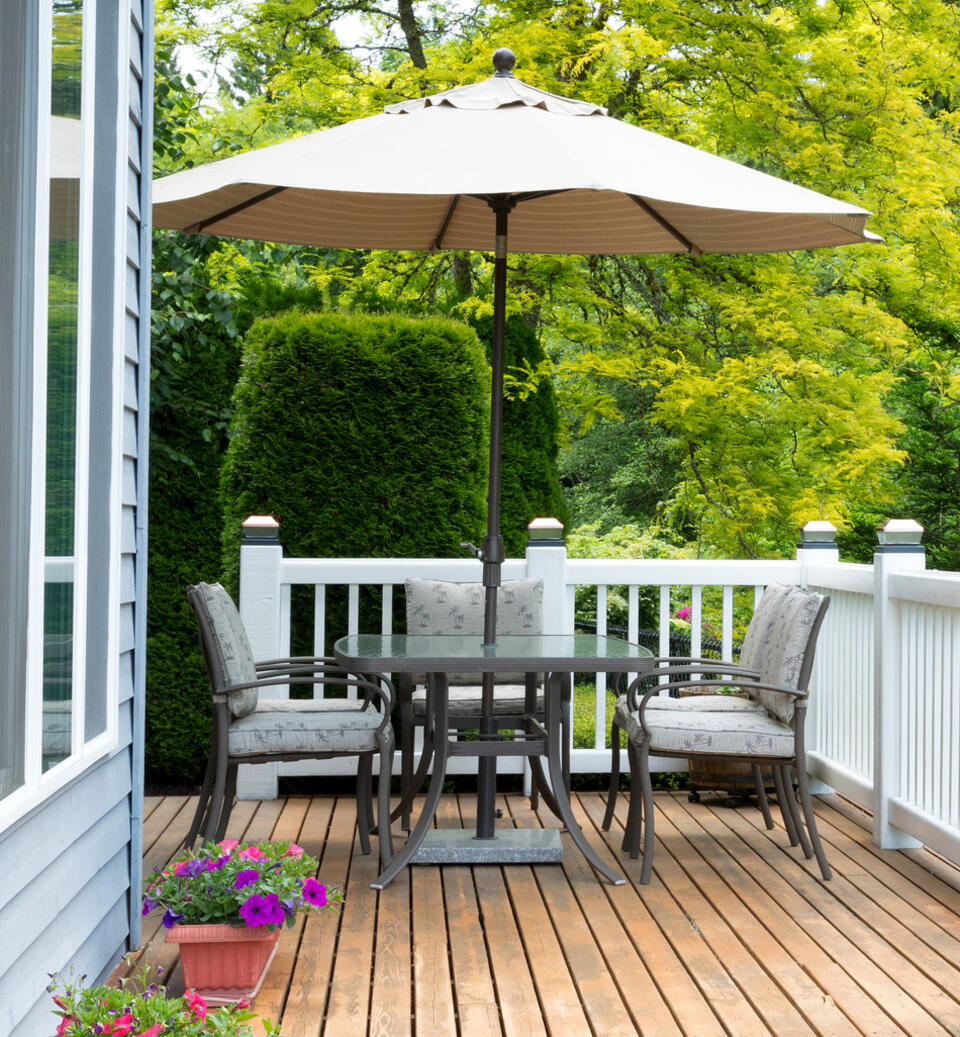 mesa de jardín con parasol redondo en una terraza