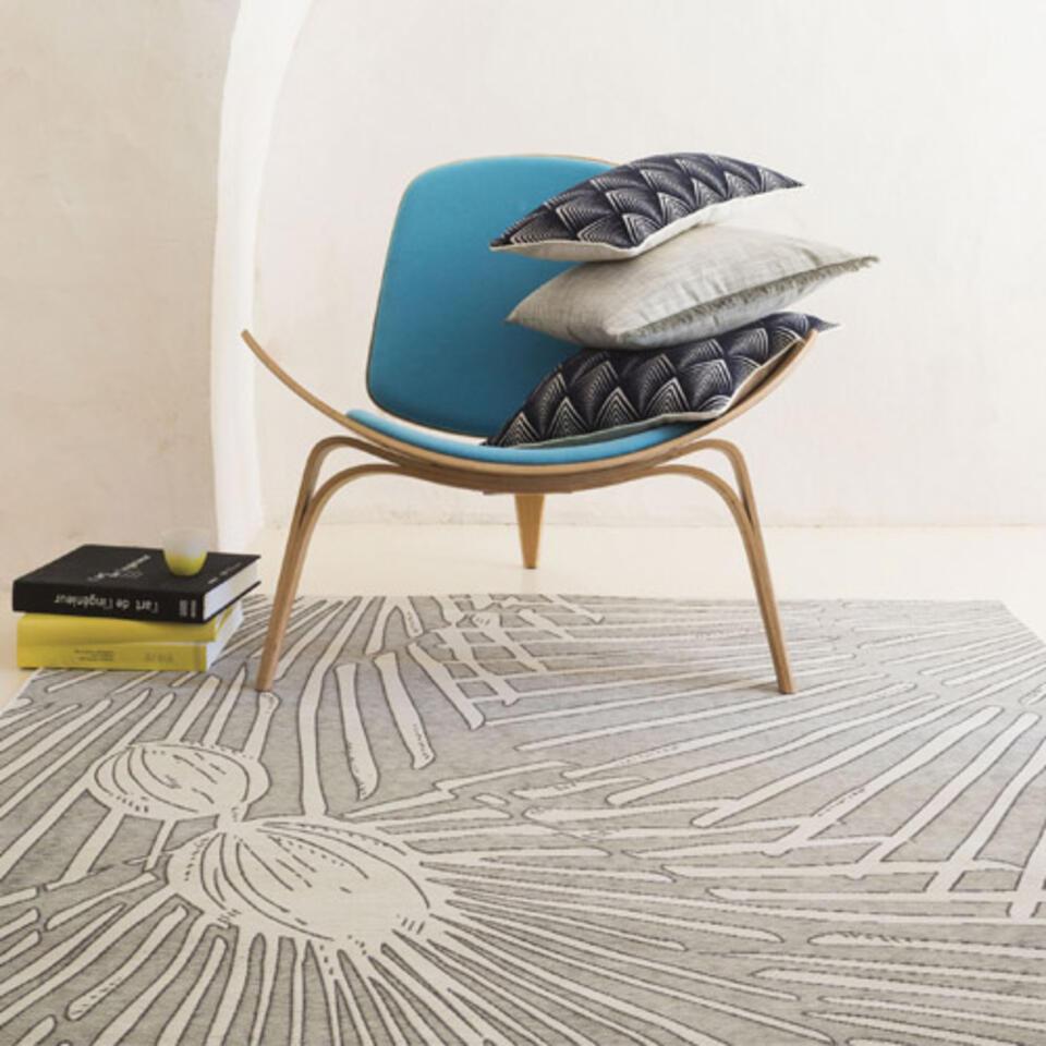 alfombra de salón gris con estampados bajo un sillón