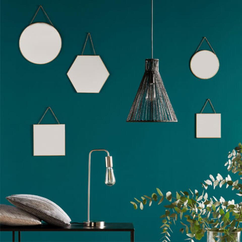 espejos redondos, hexagonales y cuadrados sobre una pared verde