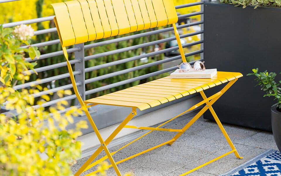 balcón con pequeño banco amarillo y plantas en maceta